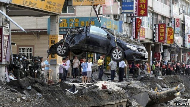 A damaged car is removed from the wreckage after an explosion in Kaohsiung