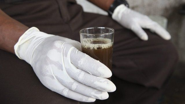 Liberian man holds a glass of Chinese tea with gloves to avoid contact with the deadly Ebola virus in Monrovia, Liberia, 31 July 2014