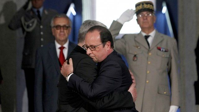 Frances President Francois Hollande (R) and German President Joachim Gauck (L) embrace as they pay their respects in the crypt of the National Monument of Hartmannswillerkopf in Wattwiller, eastern France