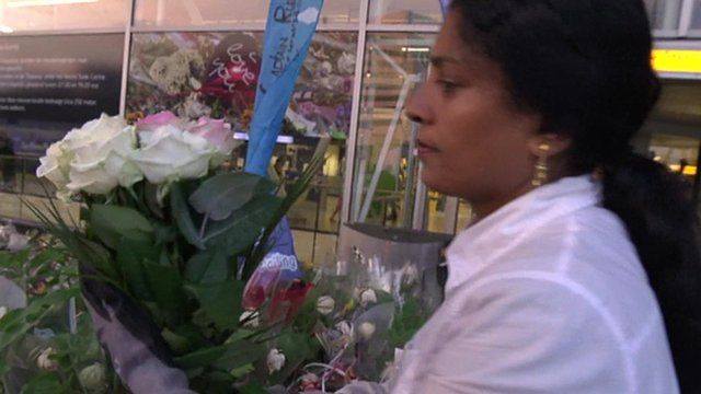 Member of staff clearing MH17 floral tributes at Schiphol airport