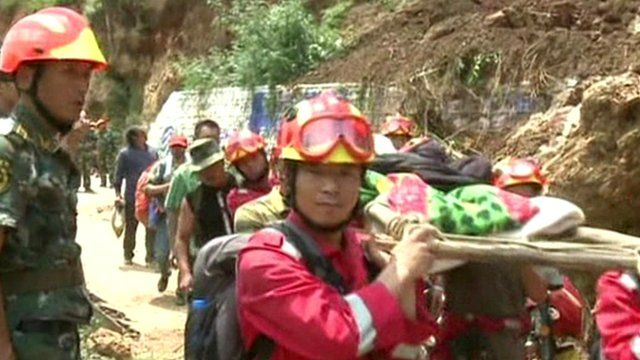 Rescuers carry woman on a stretcher