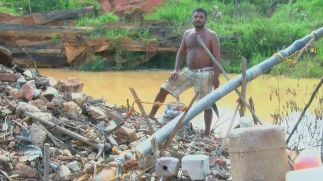 man standing on heap of rocks and rubbish next to stagnant pool