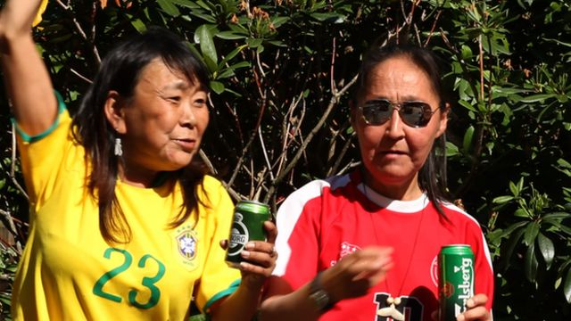 Two women in football T-shirts drinking beer. The woman on the left is cheering