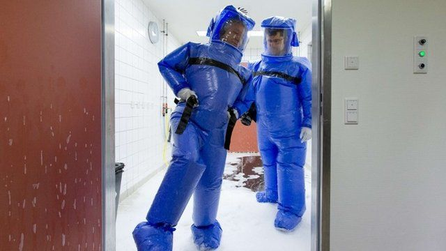 Doctor for tropical medicine Florian Steiner (R) and ward physician Thomas Klotzkowski step out of a disinfection chamber after cleaning their protective suits, at the quarantine station for patients with infectious diseases at the Charite hospital in Berlin August 11, 2014