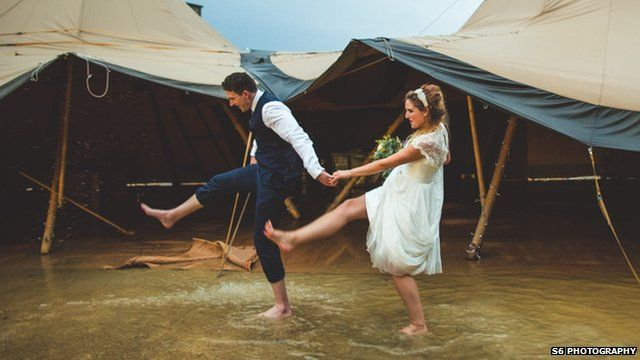 Married couple walk through the floodwater