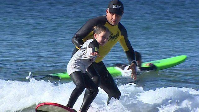Matt Grainger teaching a child to surf