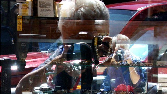 Patricia Lay-Dorsey photographing herself in the window of a shop, reflected in a mirror inside the shop