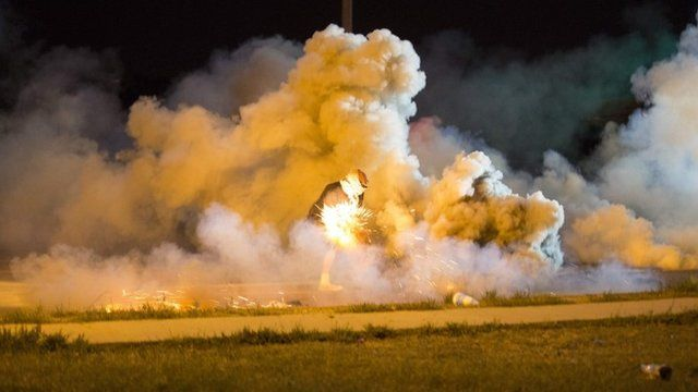 A protester throws a smoke bomb in Ferguson, Missouri