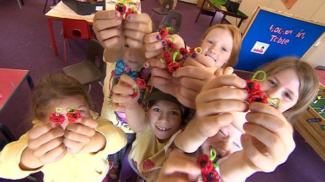 Children hold loom band poppies
