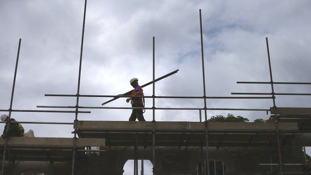 A builder carrying scaffolding on a building site
