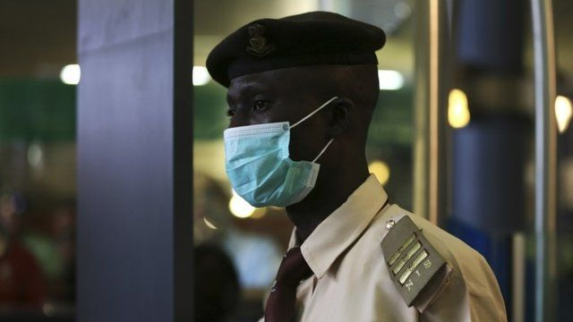 An immigration officer wears a face mask at an airport in Abuja