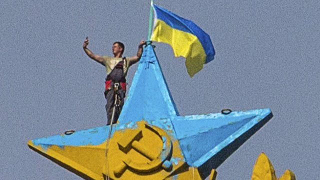 "A man takes a ""selfie"" as he stands with a Ukrainian flag on a Soviet-style star"