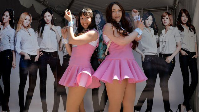 American fans of K-Pop in front of a poster for a girl band from South Korea