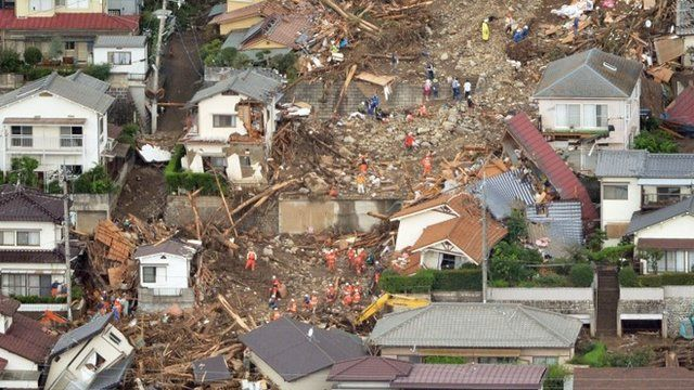 Rescuers search for survivors in the rubble in a mud-ridden residential area following a massive landslide in Hiroshima