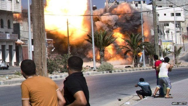 Palestinian men look on as a bomb from an Israeli air strike hits a house in Gaza City on August 23, 2014