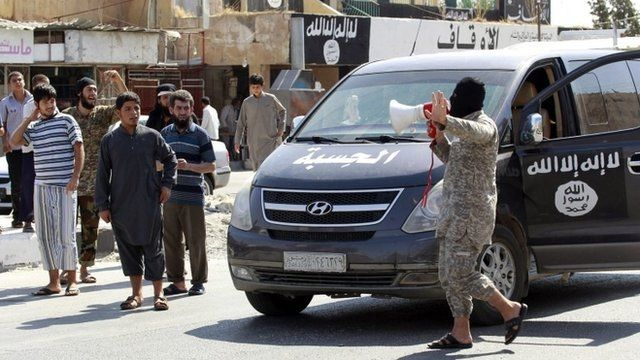 An Islamic State militant announces to residents of Taqba city that the airbase has fallen to IS