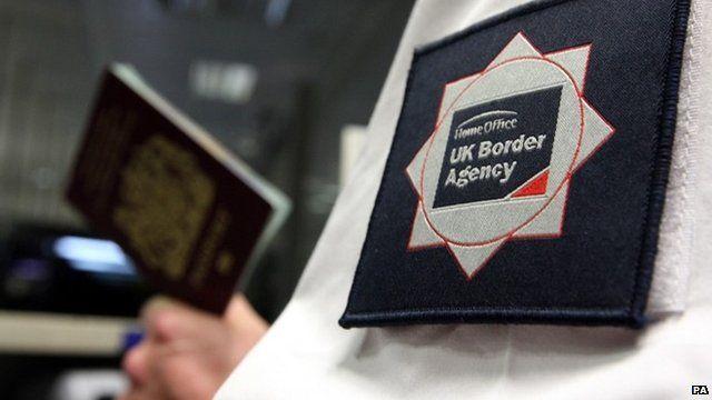 UK Border Agency officer holding a passport