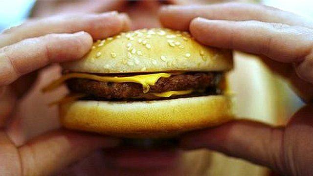 man bites into burger
