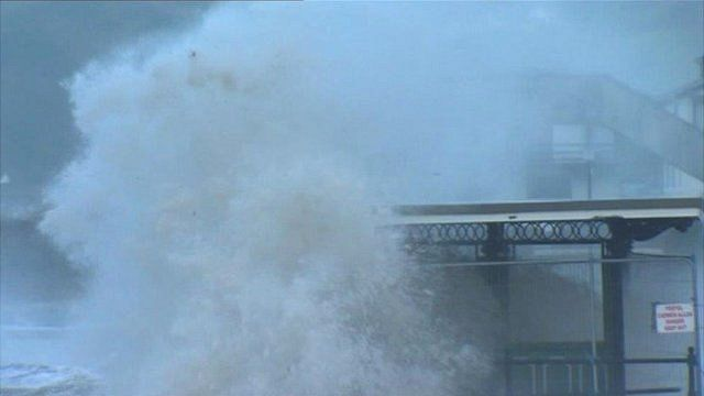 A wave crashes over a seafront shelter