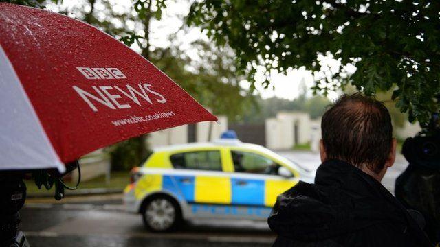 BBC News umbrella and man looking at police car