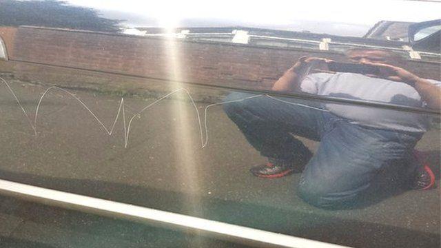 David Styles reflected in his scratched car door