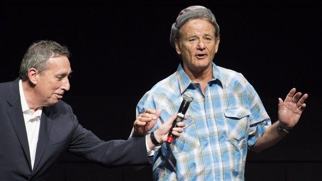 """Bill Murray sings to the crowd as producer Ivan Reitman holds a microphone following a screening of the original """"Ghostbusters"""""""