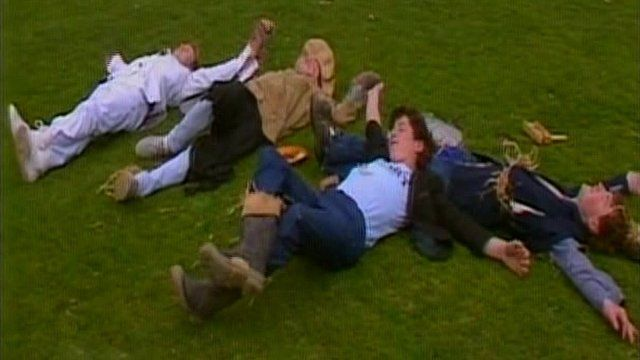 Four trainee scarecrows relax on the grass after a hard days work