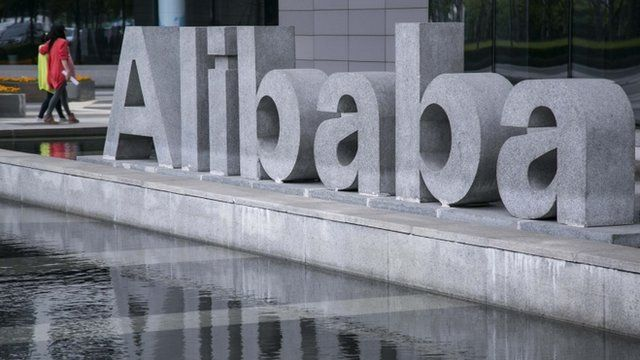 People walking past Alibaba sign