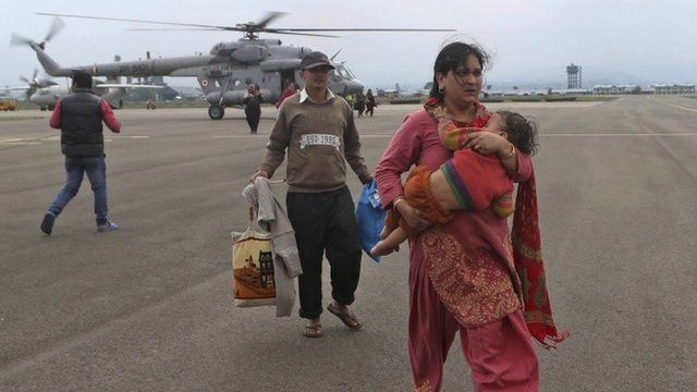 A Kashmiri flood victim, walls carrying a child after she was airlifted by the army from her flooded neighborhood to the Indian Air Force base in Srinagar, India, Monday, Sept. 8, 2014