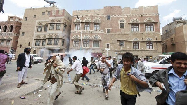 Followers of the Shiite Houthi movement flee from tear gas used by the riot police to disperse them, in Sanaa