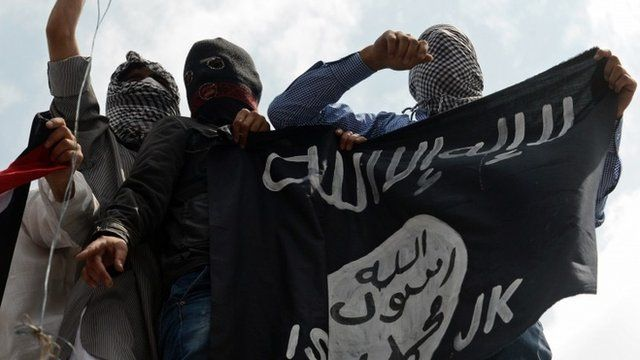 Kashmiri demonstrators hold up a flag of the Islamic State of Iraq and the Levant