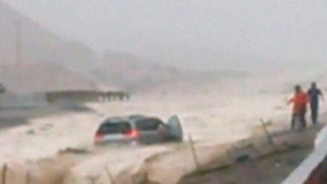 The minivan as it is swept away in flood water