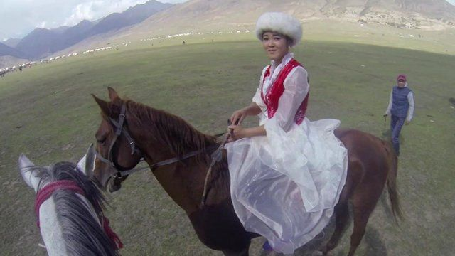 A Kyrgyz nomad girl sitting on a horse