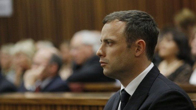 Oscar Pistorius sits in the dock while the verdict is being read