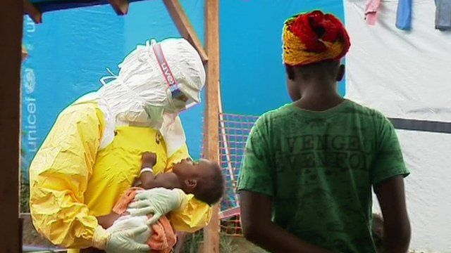 A health worker holds a baby in an Ebola hit region