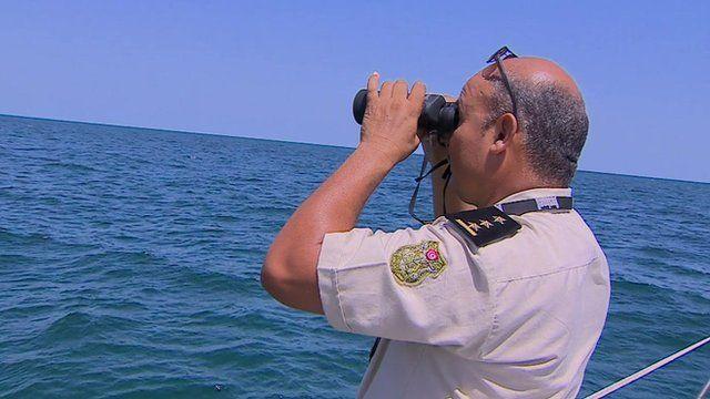 A Tunisian coast guard looks out to sea