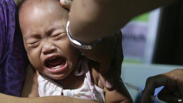A child cries as a local health worker administers a vaccine