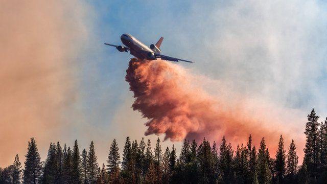 DC-10 drops fire retardant over a wildfire in California