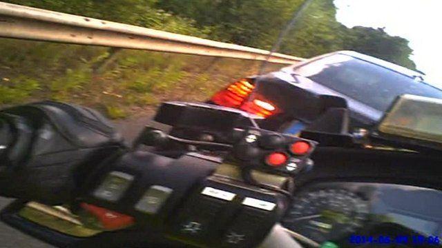 Car reversing in to police motorcycle
