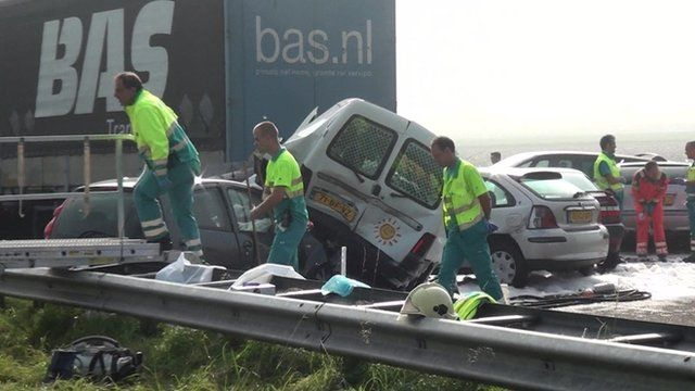 Vehicles piled on top of each other as emergency workers help at the scene