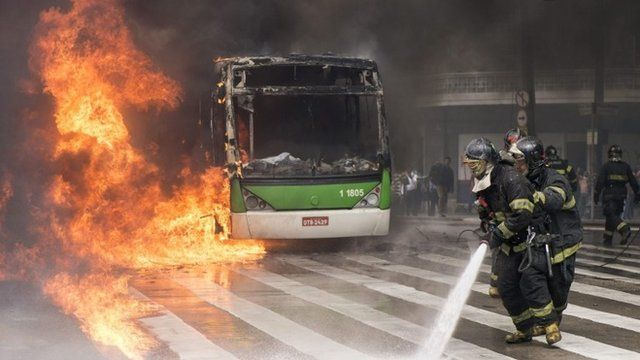 Fire-fighters work to extinguish a blaze on a bus during clashes in Sao Paulo, Brazil