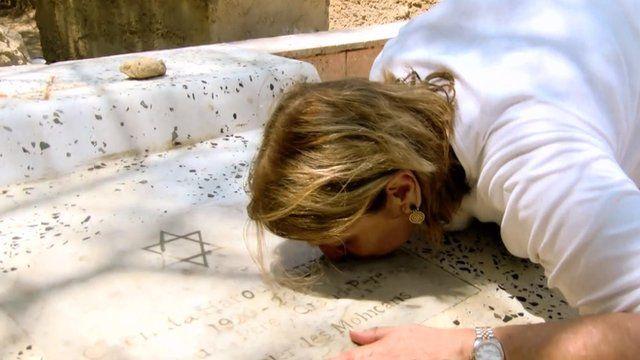 Maga Haroun kisses a grave in a Jewish cemetery