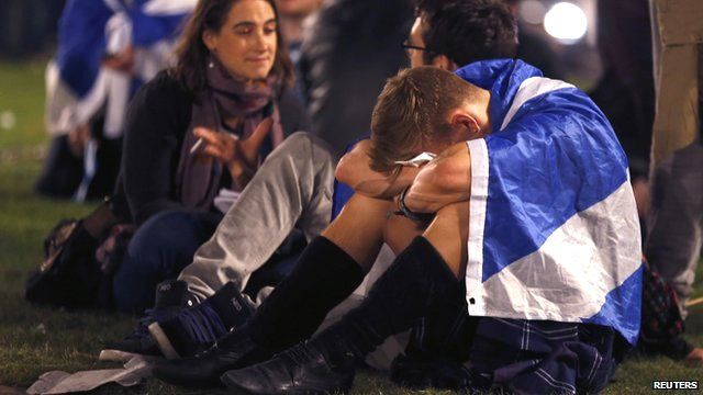 A man draped in a Scottish flag, hunched over in despair