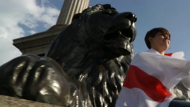 Girl wrapped in England flag sitting in front of lion statue in London's Trafalgar Square