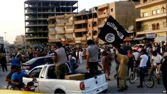 In this undated file photo posted on Monday, June 30, 2014 by the Raqqa Media Center of the Islamic State group, a militant extremist group, which has been verified and is consistent with other AP reporting, fighters from extremist Islamic State group parade in Raqqa, Syria