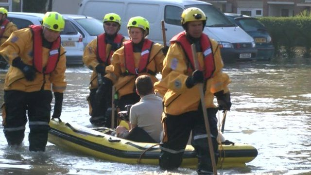 Man in a boat with emergency service workers