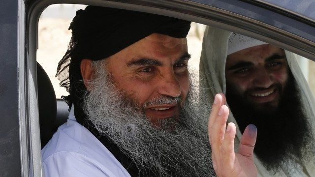 Abu Qatada (L) waves next to his son after his release from a prison near Amman