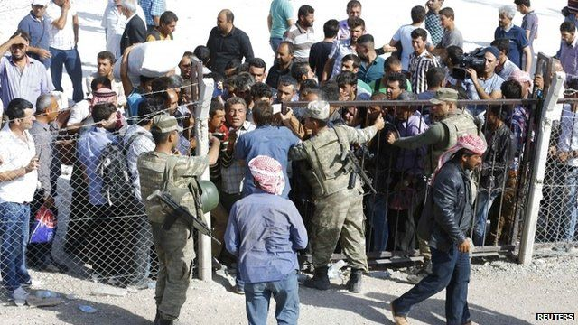 Syrian Kurds wait at Mursitpinar border crossing to return to their homes in the Syrian city of Kobani