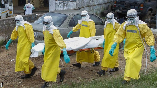 Ebola medics carry a victim's body in a bag