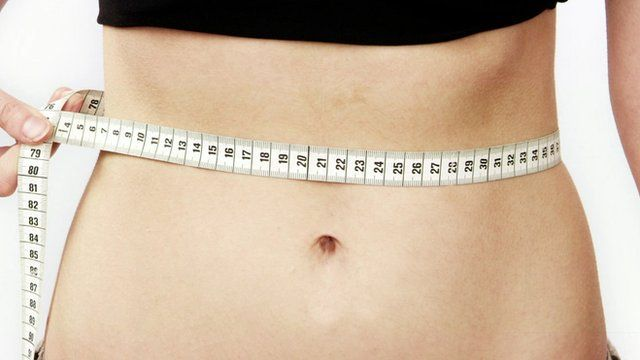 Close up of woman's bare waist with tape measure around it